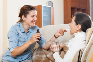 caregiver assisting senior woman in drinking her medicine