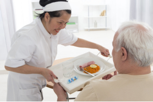 caregiver preparing breakfast to senior man